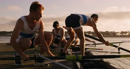 Side view of four Caucasian male rowers, squatting on a jetty, preparing oars for a training, during a sunset, in slow motion