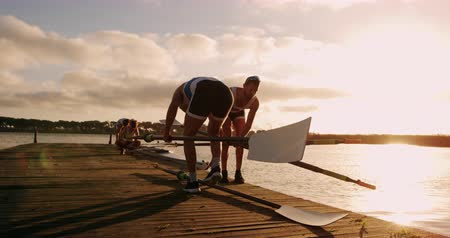 boat : Rear view close up of two Caucasian male rowers, standing on a jetty, picking up oars, with their teammates in the background, during a sunset, in slow motion