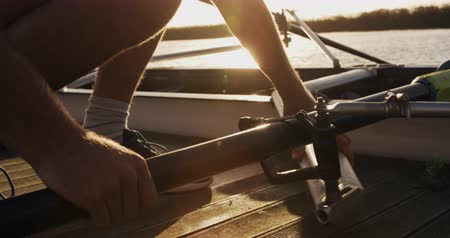squatting : Side view close up of a Caucasian male rower, squatting on a jetty, preparing oars for a training, with his teammates in the background during a sunset, in slow motion