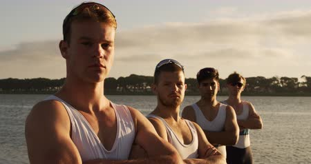adam : Side view of four Caucasian male rowers, standing in a row on a jetty, crossing arms on their chests, looking at the camera, during a sunset, in slow motion Stok Video