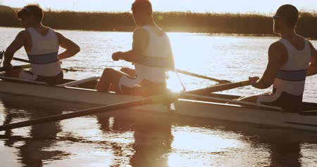 kürek çekme : Side view of four Caucasian male rowers, during a rowing practice, sitting in a boat, rowing, during a sunset, in slow motion Stok Video