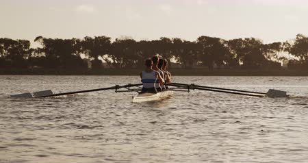 boat : Rear view of four Caucasian male rowers, during a rowing practice, sitting in a boat, rowing, during a sunset, in slow motion Stock Footage