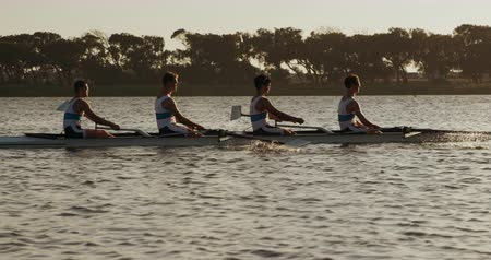 boat : Side view of four Caucasian male rowers, during a rowing practice, sitting in a boat, rowing, during a sunset, in slow motion Stock Footage