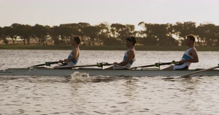 evezős : Side view close up of four Caucasian male rowers, during a rowing practice, sitting in a boat, rowing, during a sunset, in slow motion
