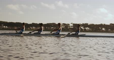 adam : Side view of four Caucasian male rowers, during a rowing practice, sitting in a boat, rowing, during a sunset, in slow motion Stok Video