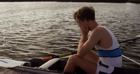 kürek çekme : Side view of a Caucasian male rower, after a rowing practise, sitting in a boat by a jetty, hiding his face in his hands, on a sunny day, in slow motion