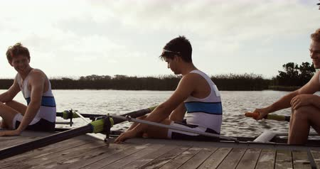 trzy : Side view of three Caucasian male rowers, after a rowing practise, sitting in a boat by a jetty, talking and discussing, on a sunny day, in slow motion