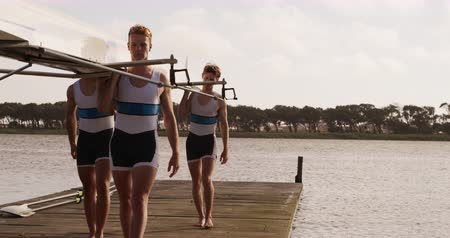 evezős : Front view of four Caucasian male rowers, standing in a row on a jetty, holding a boat on their shoulders, walking with it, on a sunny day, in slow motion