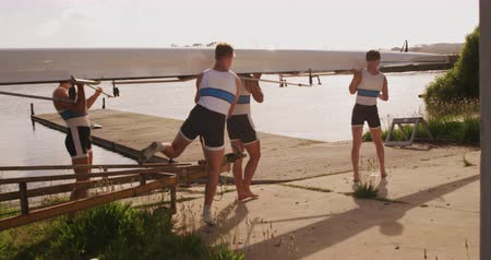 kürek çekme : Side view of four Caucasian male rowers, standing in a row on a jetty, holding a boat on their shoulders, walking with it, on a sunny day, in slow motion Stok Video