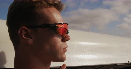 очки : Side view close up of a Caucasian male rower, wearing sunglasses with orange glasses, holding a boat on his shoulder, walking with it, on a sunny day, in slow motion