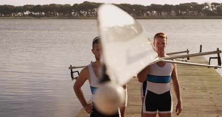 caucásico : Front view of four Caucasian male rowers, standing in a row on a jetty, holding a boat on their shoulders, walking with it, on a sunny day, in slow motion
