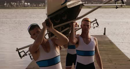 caucásico : Side view close up of four Caucasian male rowers, standing in a row on a jetty, holding a boat above their heads bottom up, putting it on their shoulders, during a sunset, in slow motion