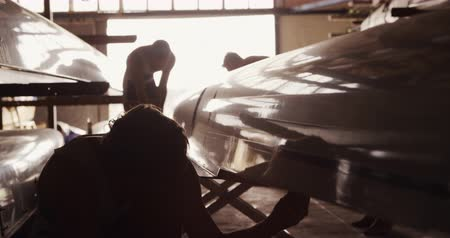 uç : Side view of three Caucasian male rowers, in a boathouse, fixing a boat, preparing it for a training, on a sunny day, in slow motion