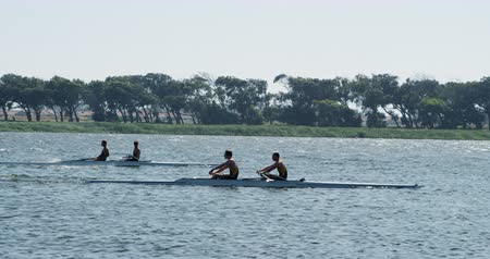 kürek çekme : Side view of two teams of two Caucasian male rowers, during a rowing practice, sitting in a boat, rowing, on a sunny day, in slow motion Stok Video