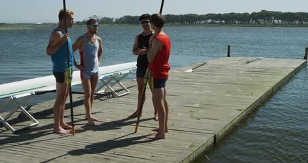 kürek çekme : Side view of four Caucasian male rowers, standing on a jetty, holding oars, talking and discussing, on a sunny day, in slow motion