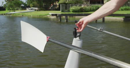 remo : Close up detail of a Caucasian male rower, preparing boat and oars to the training, on a sunny day, in slow motion