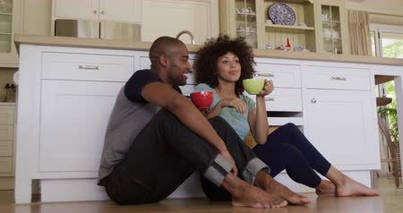 kupa : Front view of a mixed race couple enjoying time together in an apartment, sitting on a kitchen floor, holding cups, drinking tea, embracing, in slow motion. Social distancing and self isolation in quarantine lockdown