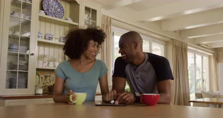 lindo : Side view of a mixed race couple enjoying their time together in an apartment, sitting by a table, drinking tea, talking, using smartphone, in slow motion. Social distancing and self isolation in quarantine lockdown