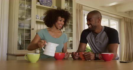kupa : Side view of a mixed race couple enjoying their time together in an apartment, sitting by a table, a woman is poring milk into a bowl, in slow motion. Social distancing and self isolation in quarantine lockdown