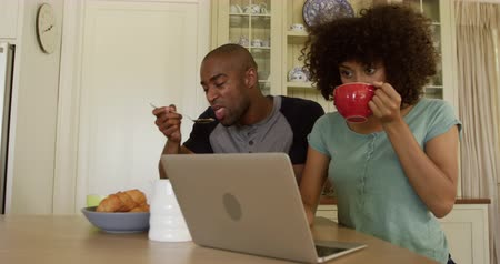 lindo : Side view of a mixed race couple enjoying their time together in an apartment, sitting by a table, a man is eating cereal, while a woman is drinking tea and using laptop, in slow motion. Social distancing and self isolation in quarantine lockdown Archivo de Video