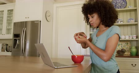 kupa : Side view of a mixed race woman enjoying her time in an apartment, sitting by a table, drinking tea and using laptop, in slow motion. Social distancing and self isolation in quarantine lockdown