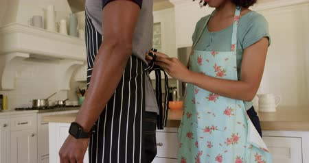 kuchnia : Side view mid section of a mixed race couple enjoying their time together in an apartment, standing in a kitchen, a woman is tying mans apron, in slow motion. Social distancing and self isolation in quarantine lockdown Wideo