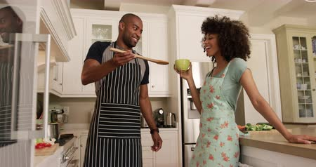 adam : Side view of a mixed race couple enjoying their time together in an apartment, standing in a kitchen, wearing cooking aprons, a woman is holding a cup of tea, while a man is cooking and giving her a taste, in slow motion. Social distancing and self isolat