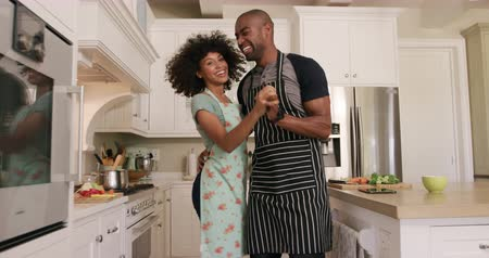 kuchnia : Side view of a mixed race couple enjoying their time together in an apartment, standing in a kitchen, wearing cooking aprons, cooking, dancing, in slow motion. Social distancing and self isolation in quarantine lockdown