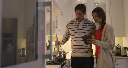 kuchnia : Side view of a Caucasian couple enjoying their time together in an apartment, standing in a kitchen, a woman is holding a digital tablet, while a man is cooking, in slow motion. Social distancing and self isolation in quarantine lockdown Wideo