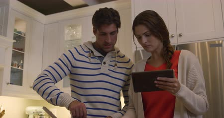 lindo : Front view close up of a Caucasian couple enjoying their time together in an apartment, standing in a kitchen, a woman is holding a digital tablet, while a man is cooking, in slow motion. Social distancing and self isolation in quarantine lockdown