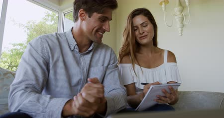 молодой человек : Front view of a Caucasian couple enjoying their time together, sitting on a couch in an apartment, holding paperwork, discussing and smiling, in slow motion