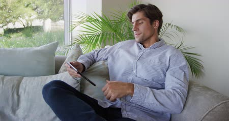 jedna osoba : Side view of a Caucasian man enjoying his time in an apartment, sitting on a couch, holding a smartphone, in slow motion