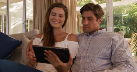 молодой человек : Front view close up of a Caucasian couple enjoying their time together in an apartment, sitting on a couch, a woman is holding a digital tablet and is pointing at it, smiling, in slow motion Стоковые видеозаписи