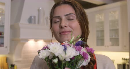 kuchnia : Front view close up of a Caucasian woman enjoying her time in an apartment, holding a bouquet of flowers, smelling them, in slow motion. Social distancing and self isolation in quarantine lockdown