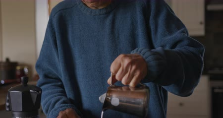 rövid : Social distancing and self isolation in quarantine lockdown. Front view close up of a senior Caucasian woman with short grey hair relaxing at home in her kitchen, standing at the counter making coffee, pouring milk from a jug into her cup, slow motion