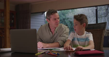 schoolbook : Social distancing and self isolation in quarantine lockdown. Home schooling. Caucasian man and his young son at home in the living room, sitting at a table talking, the father helping his son with homework, open schoolbooks and a laptop computer on the ta