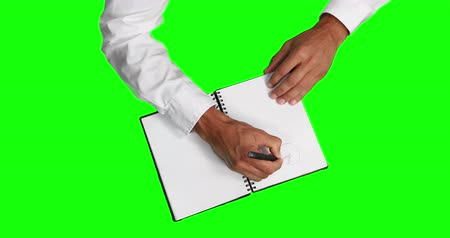 informação : Overhead mid section view of a Caucasian businessman wearing white shirt, explaining a paperwork, drawing graphs in a notebook, on green screen background.