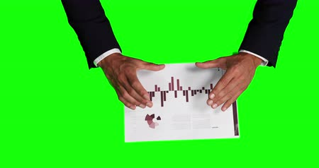 firma : Overhead mid section view of a Caucasian businessman wearing white shirt and black suit, explaining graphs printed on a piece of paper, on green screen background. Wideo