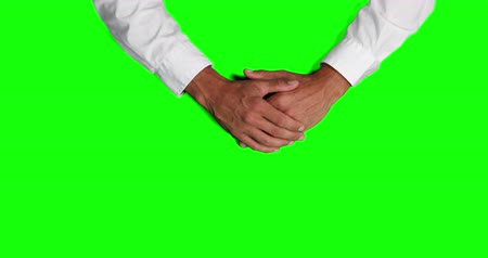 firma : Overhead mid section view of a Caucasian businessman wearing white shirt, explaining his work, holding hand on hand, on green screen background. Wideo