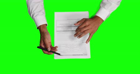 firma : Overhead mid section view of a Caucasian businessman wearing white shirt, explaining a paperwork, writing on a piece of paper, on green screen background.