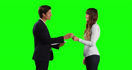 firma : Side view of a Caucasian male sales advisor holding a file, giving car keys to a Caucasian female lessor, smiling and shaking hands, on green screen background Wideo
