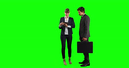 verbinden : Side view of a Caucasian businesswoman holding a tablet and businessman holding a bag, standing and discussing a deal, smiling and shaking hands, on green screen background.