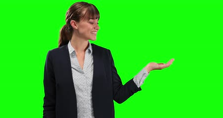 mutlu : Side view of a happy Caucasian businesswoman with long dark hair holding her hand out as if holding an object on green screen background