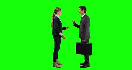 firma : Attractive Caucasian businesswoman holding a tablet and businessman holding a bag, standing and discussing a deal, smiling and shaking hands, on green screen background.
