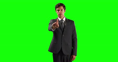 firma : Front view of a Caucasian businessman wearing smart clothes, with arm raised and hand out in front of him, with his index finger facing camera, touching a virtual interactive screen on green screen background.