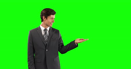 firma : Side view of a Caucasian businessman wearing smart clothes, holding his hand out as if holding an object on green screen background Wideo