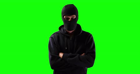 muž : Portrait of a Caucasian man wearing a black hooded top and black balaclava covering his face, standing with his arms crossed and looking straight into a camera on green screen background. Dostupné videozáznamy