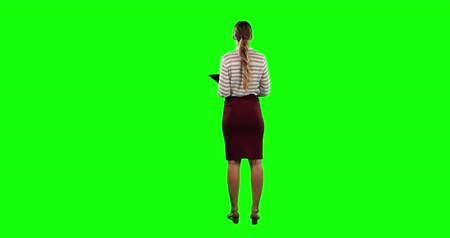 firma : Rear view of a Caucasian businesswoman with long hair, wearing smart clothes, standing with her hand put on her hip, holding a tablet, on green screen background.