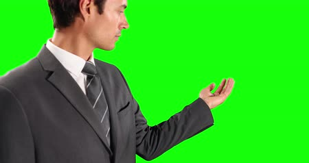 firma : Side view close up of a Caucasian businessman wearing smart clothes, holding his hand out as if holding an object on green screen background