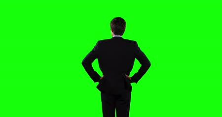 firma : Rear view of a Caucasian businessman with dark short hair, wearing smart clothes, standing with his hands put on his hips, on green screen background. Wideo